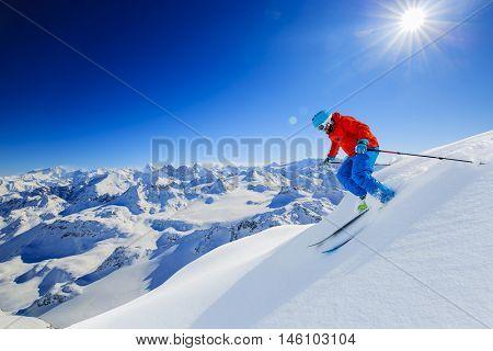 Skier skiing downhill in high mountains in fresh powder snow. Snow mountain range in background. Mt Fort Peak Alps region Switzerland.