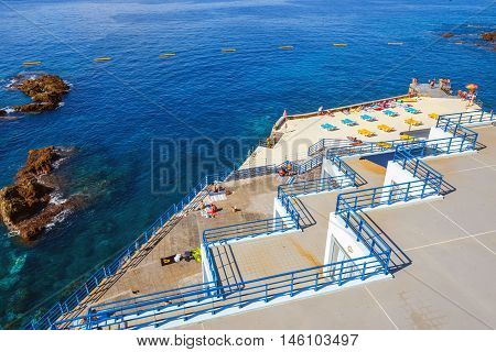 Funchal Madeira - July 6 2016: Unidentified people sunbathing on the city beach in Funchal Madeira Island Portugal