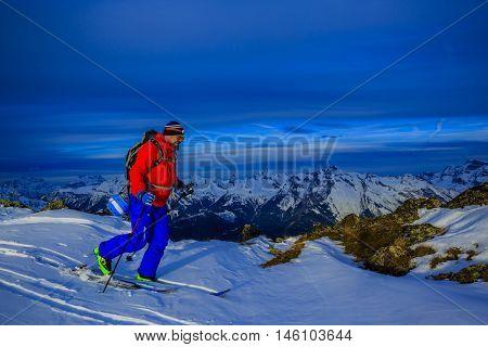 Ski touring in high mountains in fresh powder snow before sunrise. Snow mountain range. Mt Fort Peak Alps region Switzerland.Wallis