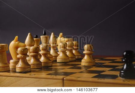 Playing wooden chess. White pawn against the rest of the figures