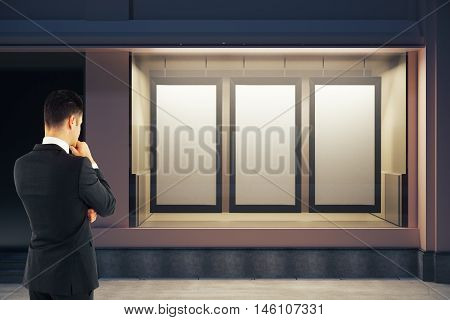 Back view of thoughtful businessman looking at showcase with three blank posters at night. Mock up 3D Rendering