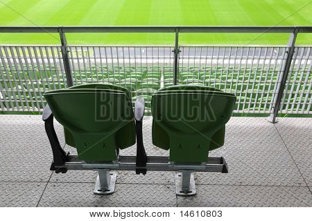 Two green plastic seats on tribune of large stadium, behind
