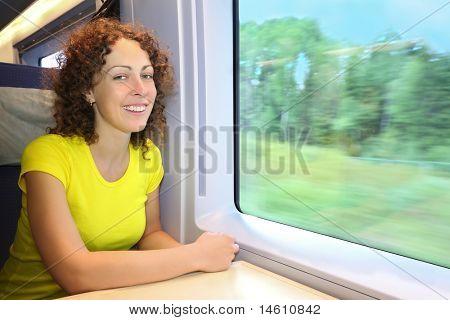 Woman rides in  speed train near window