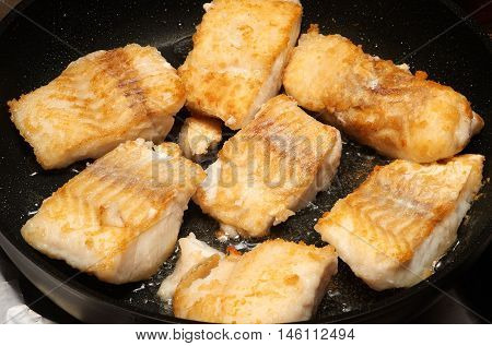 Fried cod fillet pieces on the frying pan