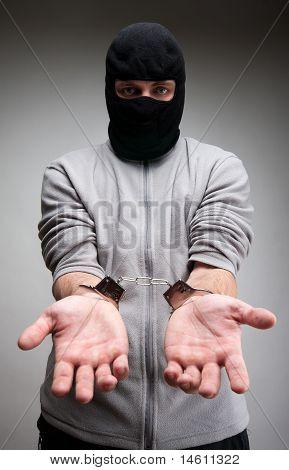 Criminoso algemado pedindo liberdade