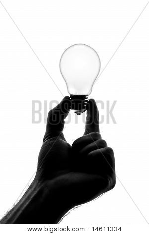 Silhouette Of Hand Holding Dull Bulb