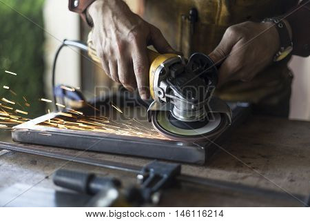 A man grinds the welding seam off of steel.