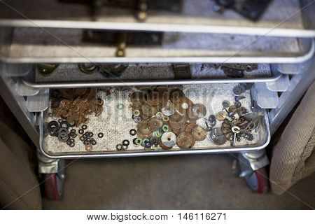 Various tarnished antique hardware pieces dry on shelving.