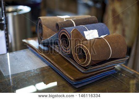 Freshly sized and cut leather sits at a bookbinders workstation.