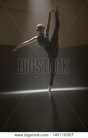 Cute ballet dancer stands on one leg with second outstretched up in the dance hall. She dressed in the ballet suit. Light falls on her crown and arm. Shoot in a low key.