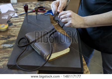 A bookbinder threads the leather strap through the cover by hand.