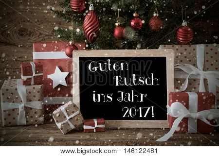 Nostalgic Card For Seasons Greetings. Christmas Tree With Balls And Snowflakes. Gifts In The Front Of Wooden Background. Chalkboard With German Text Guten Rutsch Ins Jahr 2017 Means Happy New Year