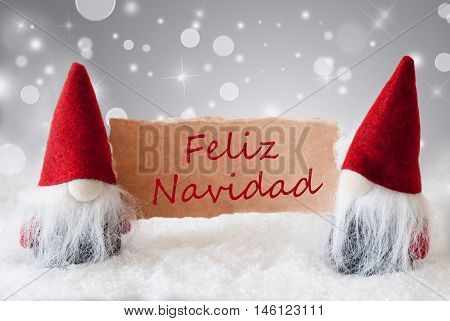 Christmas Greeting Card With Two Red Gnomes. Sparkling Bokeh And Noble Silver Background With Snow. Spanish Text Feliz Navidad Means Merry Christmas