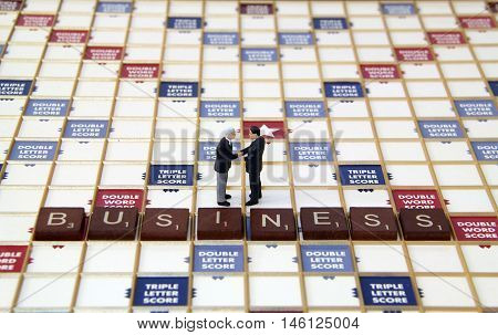Two business men figurines on a scrabble baord game closing a business deal.