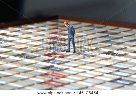 Business man figurine standing on a scrabble game board looking at the center square.