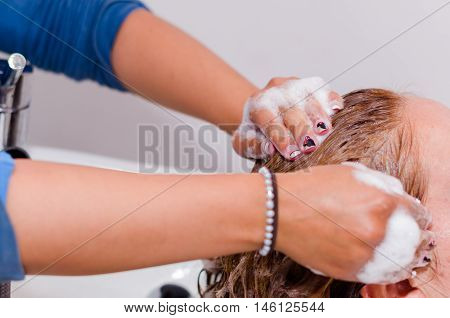 Massages inside a hairdressing saloon, hands washing with a nice shampoo a long hair.