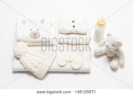 baby child clothing on white studio shot warm shouse teddy bear sweater hat bottle of milk mittens  baby fashion