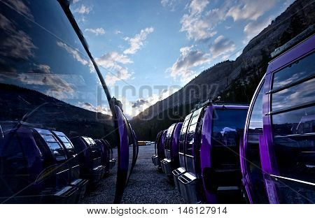 Chair lift cars with clouds reflection in windows. Rocky Mountains. Alblerta. Canada.