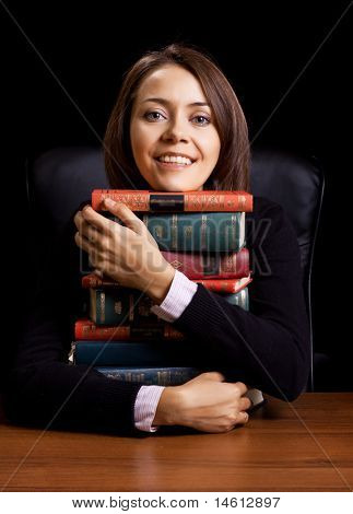 young woman with many books at the desk on black background