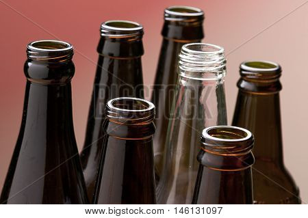 Tops of empty glass bottles. A close up of several brown glass bottles and one clear glass bottle.