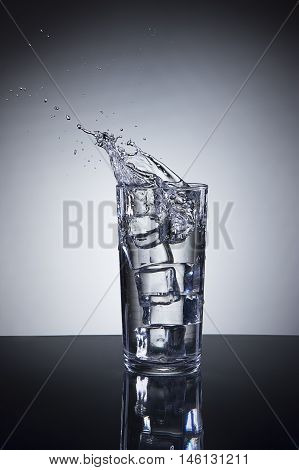 Small splash in water glass. Ice being dropped into a glass of water making a splash.