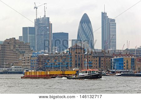 LONDON UNITED KINGDOM - JANUARY 25: Barges Towed by a Tugboat on the River Thames in London on JANUARY 25 2013. Transporting Waste by Water in Sealed Containers on Barges Which are Pulled by Tug in London United Kingdom.