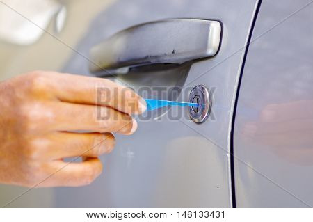 Closeup hands of locksmith using pick tools to open locked car door.