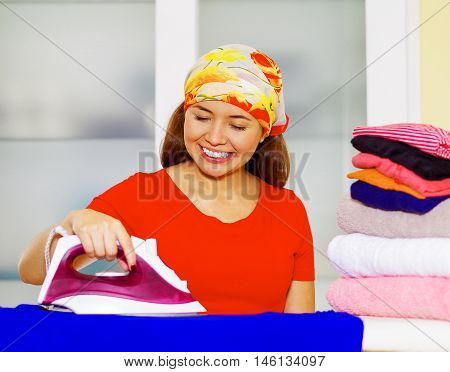 Young charming woman with colorful headscarf ironing stack of clothes while smiling happily, laundry housework concept,