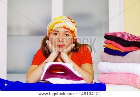 Young charming woman with colorful headscarf resting head in her own hands looking into camera, laundry housework concept.