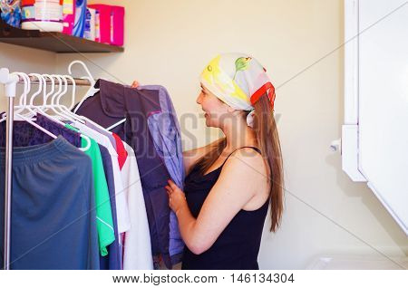 Charming young woman wearing colorful headscarf standing inside wardrobe looking through selection og clothes hanging, laundry housework concept.