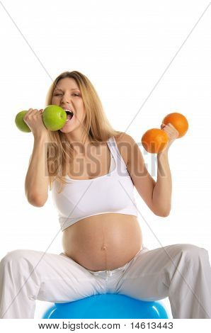 Pregnant woman bites dumbbell fruit