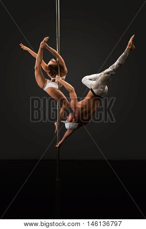 Studio photo of sporty people dancing on pole in pair