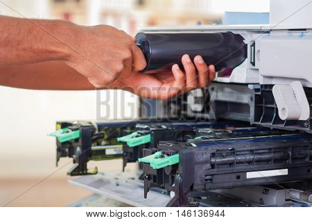 Closeup hand in front of open photocopier during maintenance repairs using handheld tool, black mechanical parts.