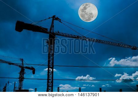 Silhouette of tower cranes on the construction site with bright full moon at nighttime. Beautiful blue sky with cloud and full moon background. The moon were NOT furnished by NASA.