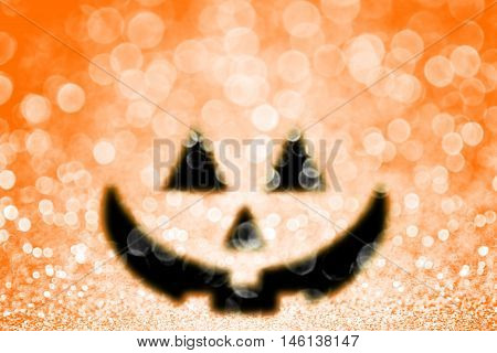 Abstract happy Halloween orange pumpkin jack o lantern glitter sparkle background or trick or treat party invite