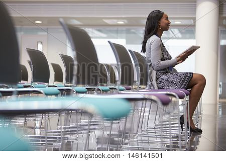 Businesswoman In Empty Auditorium Preparing To Make Speech