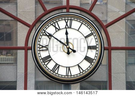 Clock with roman numerals for hours hands at nine minutes to twelve o'clock on a glass wall building in background