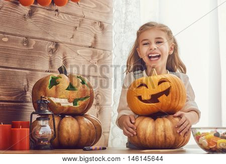 Happy halloween! Cute little child girl with carving pumpkin. Happy family preparing for Halloween.