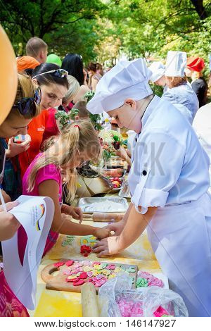 Zaporizhia/Ukraine- September  3, 2016: Charity festival for children - City of professions . Children making colorful gum paste berry shaped decorations, cooking workshop outdoors.