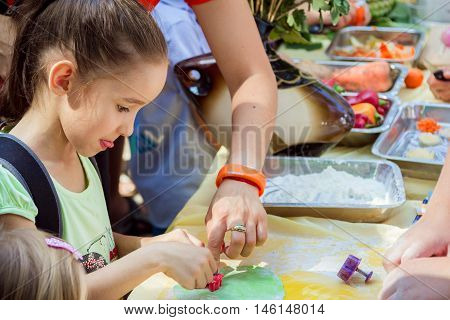 Zaporizhia/Ukraine- September  3, 2016: Charity festival for children - City of professions . Girl participating in cooking workshop, concentrated on making colorful gum paste decorations.
