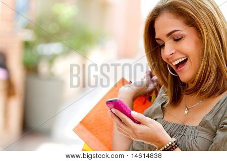 Beautiful shopping woman texting on her cell phone