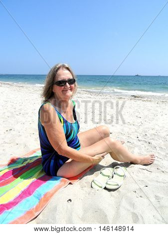Mature female blond beauty relaxing on the beach.