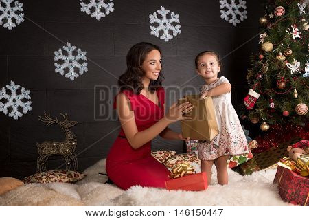 Happy mother with small surprised child being given a Christmas gift.
