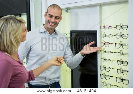 Optician helping customer for selecting a spectacles frame in optical store