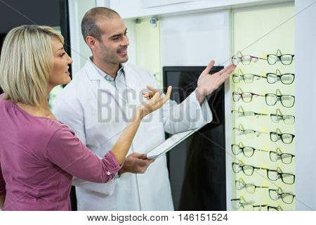 Optometrist consulting a customer about spectacles and frames in optical store
