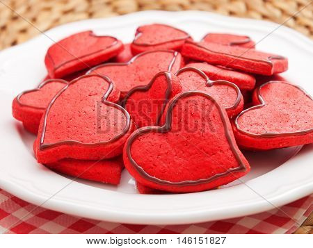 Homemade heart-shaped red cookies decorated with chocolate frosting. Horizontal shot