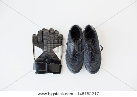 sport, soccer, football and sports equipment concept - close up of goalkeeper gloves and boots