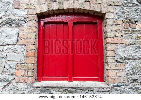 architecture concept - close up of red vintage wooden window shutter in old stone wall
