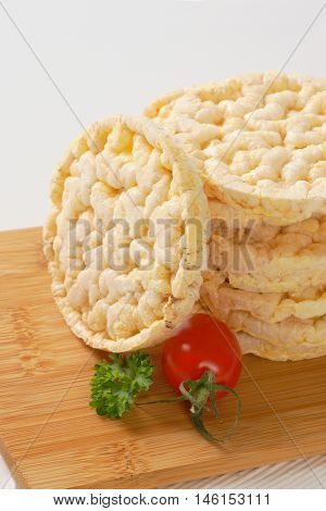 stack of puffed rice bread slices on wooden cutting board