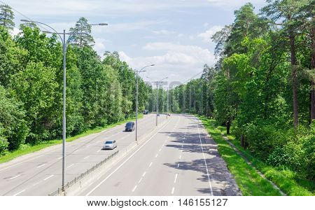 View of the motorway with asphalt surface lampposts traffic barriers and forest on both sides in summer day